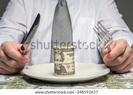 Businessman sitting behind a table with fork and knife ready to eat a wad of dollars served on plate - business concept - stock photo