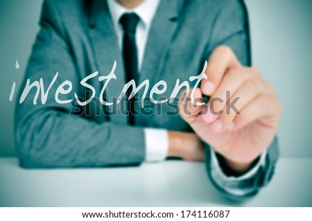 businessman sitting in a desk writing the word investment in the foreground - stock photo