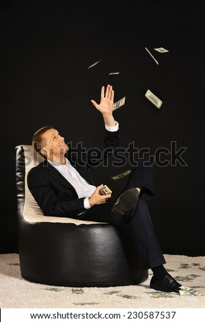 Businessman sitting in armchair with a lot of money - stock photo