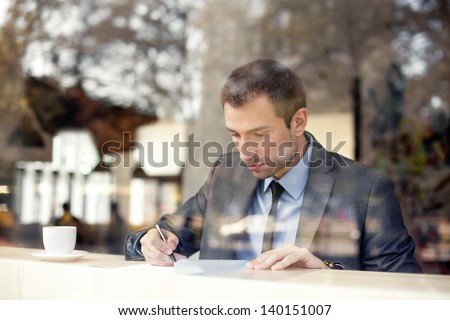 Businessman sitting in coffee shop, signing contract - stock photo