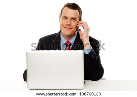 Businessman sitting in front of laptop on work desk and talking on cell phone - stock photo