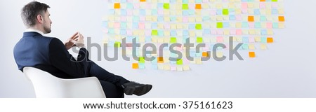 Businessman sitting in front of sticky notes wall, panorama - stock photo