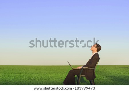 businessman sitting in green field, feeling relax - stock photo