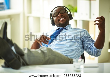 Businessman sitting in headphones in office - stock photo