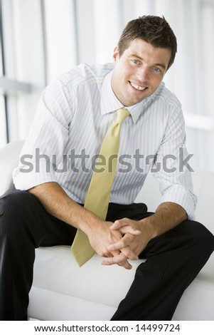 Businessman sitting in office lobby smiling - stock photo
