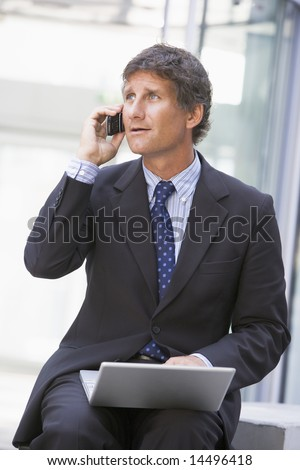 Businessman sitting in office lobby with laptop using cellular phone - stock photo