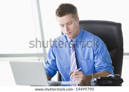 Businessman sitting in office with laptop writing note - stock photo