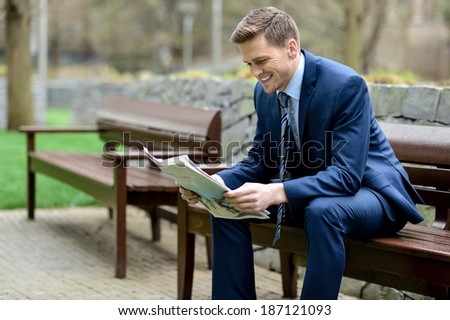Businessman sitting in park bench, reading a newspaper - stock photo