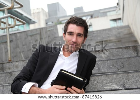 Businessman sitting in stairs out in town - stock photo