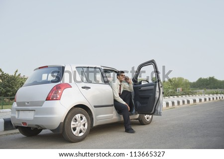 Businessman sitting in the car and talking on a mobile phone - stock photo