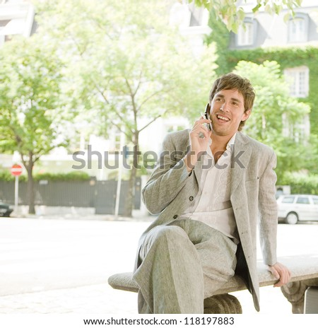 Businessman sitting on a bench in the financial district, using his cell phone while sitting on a bench in the financial district with office buildings in the background, outdoors. - stock photo