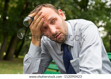 Businessman sitting on a bench in the park. - stock photo