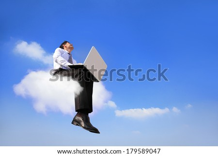 businessman sitting on a cloud working with laptop, low angle view, cloud computing concept - stock photo