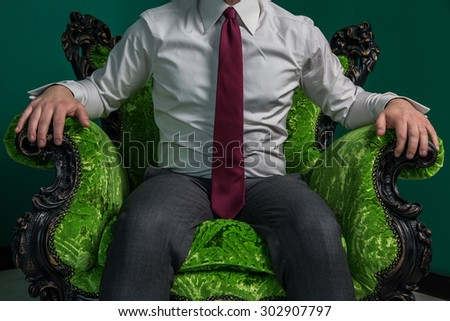 businessman sitting on a green armchair vintage - stock photo