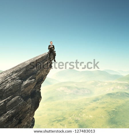 Businessman sitting on a peak with cup of coffee - stock photo