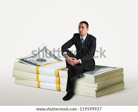 Businessman sitting on a stack of dollars - stock photo