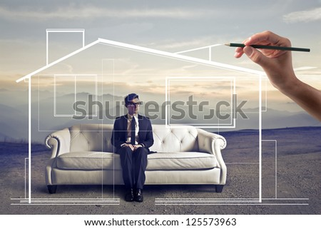 Businessman sitting on a white sofa in a wasteland, a hand drawing around him an home - stock photo