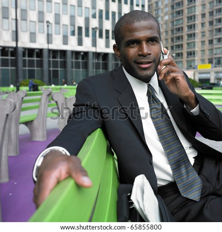 Businessman sitting on bench talking on cell phone - stock photo