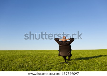 Businessman sitting on green grassland under blue sky - stock photo