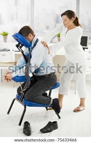 Businessman sitting on massage chair, getting back massage.? - stock photo