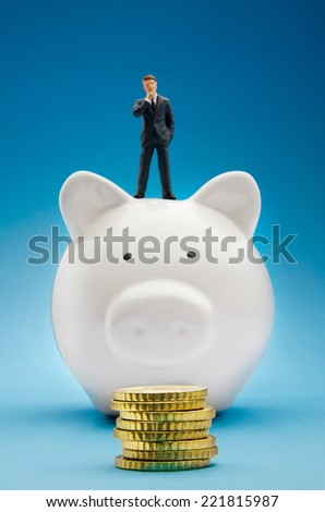 Businessman sitting on piggy bank in front of a stack of coins - stock photo