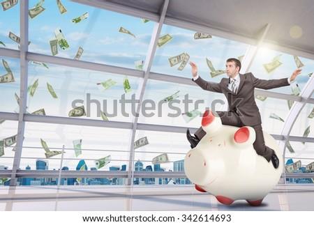 Businessman sitting on piggy bank on office background - stock photo