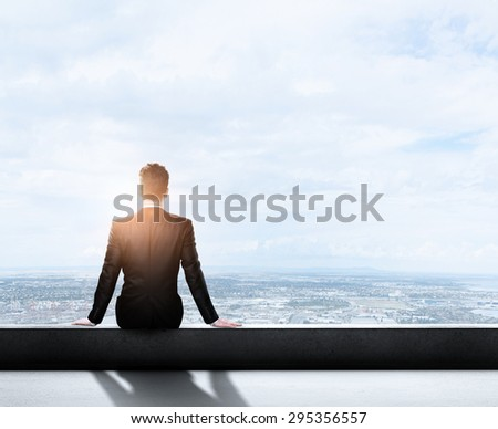 businessman sitting on roof and clouds in sky - stock photo