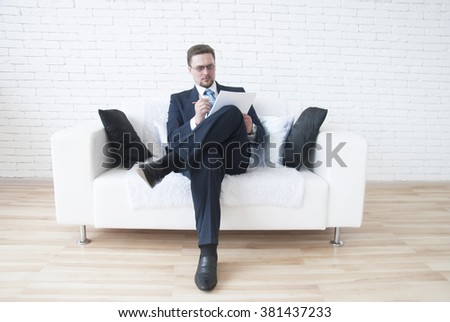 Businessman sitting on sofa and signing a contract - stock photo
