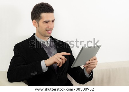 Businessman sitting on sofa and using a digital tablet pc. - stock photo