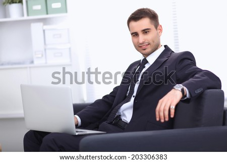 Businessman sitting on sofa in the office - stock photo