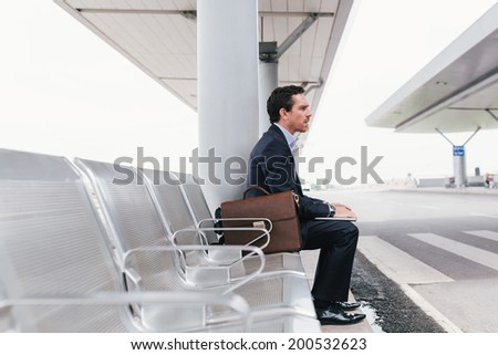Businessman sitting on the chair at the airport bus stop and looking away, side view - stock photo