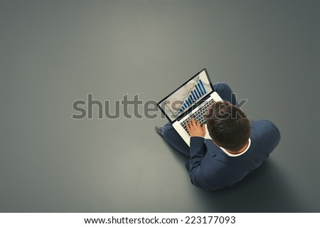 businessman sitting on the dark floor with laptop, typing and looking at growing diagram. view from above - stock photo