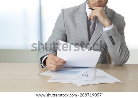 Businessman sitting table and holding document - stock photo