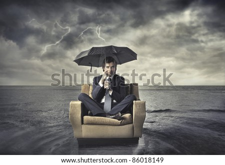 Businessman sitting under an umbrella on an armchair in the middle of the sea - stock photo