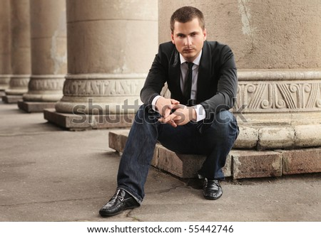 businessman sitting under column - stock photo