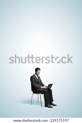 businessman sitting with laptop on blue background - stock photo