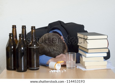 Businessman sleeping at his desk, surrounded by books, drugs and alcohol. - stock photo
