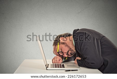 Businessman sleeping on a laptop on grey office wall background  - stock photo
