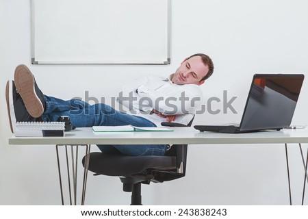 Businessman sleeping on the job at work - stock photo