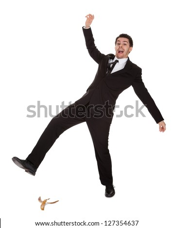 Businessman slipping on banana peel. Isolated on white - stock photo