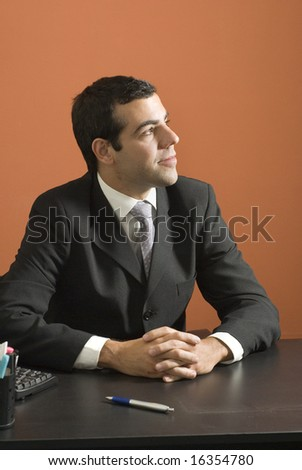 Businessman smiles as he looks off in distance while sitting at his desk. Vertically framed photo. - stock photo