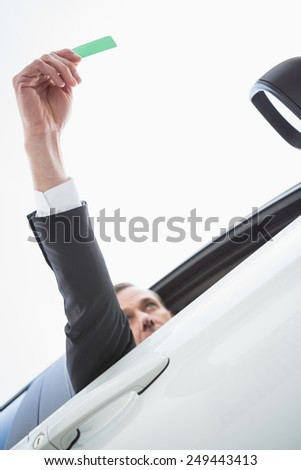 Businessman smiling and holding card in his car - stock photo