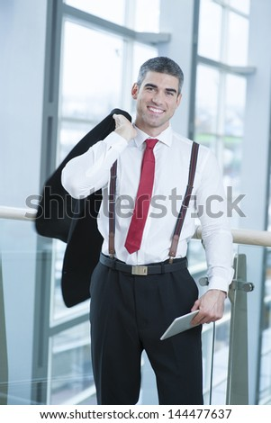 Businessman smiling and looking at camera with jacket over shoulder - stock photo