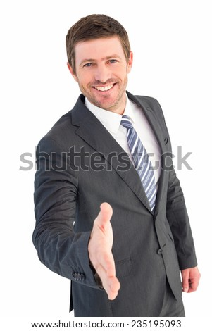 Businessman smiling and offering his hand on white background - stock photo