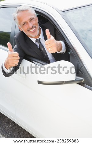 Businessman smiling at camera showing thumbs up in his car - stock photo
