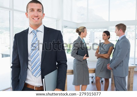 Businessman smiling at camera with colleagues behind him in the office - stock photo