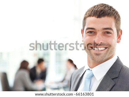 Businessman smiling at the camera while his team is working in the background - stock photo