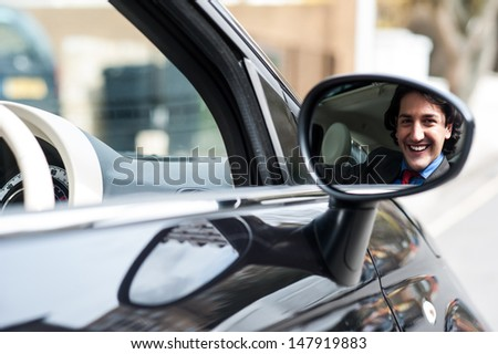 Businessman smiling in rear view mirror - stock photo