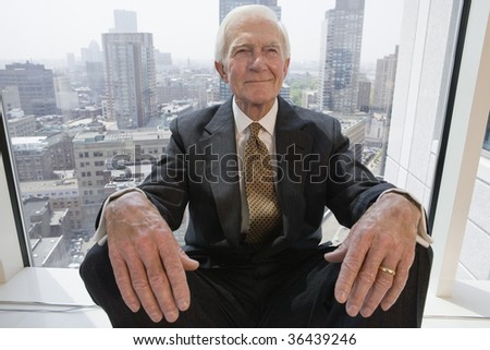 Businessman smiling while sitting in a window. - stock photo