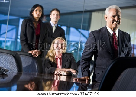 Businessman smiling with colleagues behind - stock photo
